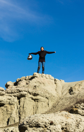 climbed: Girl motorcycle rider climbed on a rocky hill with her gear and motorcycle helmet in hand cheering with raised hands Stock Photo