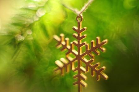 Christmas tree decoration. Snowflake hanging on twine. Bokeh background.Christmas tree twig. Stock Photo