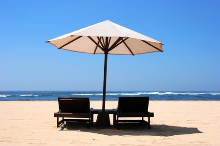 Two chaise lounges under an umbrella on sandy to an ocean coast photo