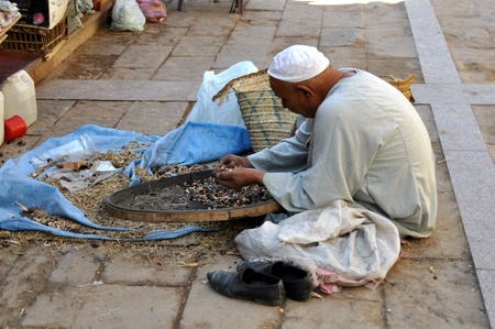 man nuts: Egypt, Aswan - on September, 21st 2010: the Egyptian man, touches nuts for sale in a peace life in streets of the city of Aswan.