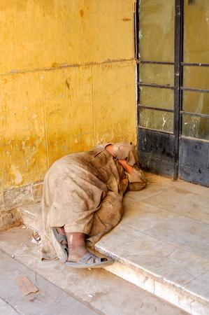 hombre pobre: ASWAN, EGYPT - SEPTEMBER 21,2010: a Poor man sleeping on the pavement in Aswan