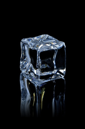 solid blue background: ice cube on the black  background with reflection