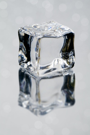 ice cube on the gray background with reflection and bokeh lights photo
