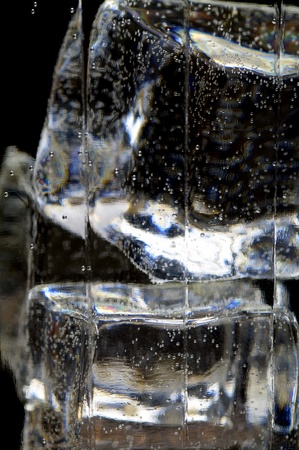 wasser: part of glass with ice cubes and liquid with bubbles macro blur Stock Photo