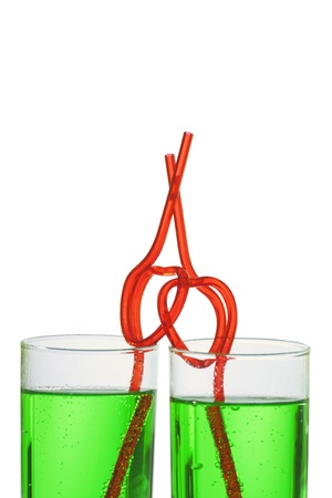 two glasses with green beverage and drinking straws photo