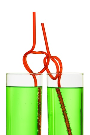 two glasses with green beverage and drinking straws isolated on white background photo