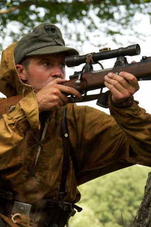 man in form of nazi sniper aims near a tree on celebration of 750 anniversary of Guryevsk (Neuhausen O.P.) on June 30, 2012 in Guryevsk, Kaliningradskaya oblast, Russia