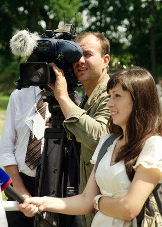 correspondent: GURYEVSK, KALININGRADSKAYA OBLAST, RUSSIA - JUNE 30: cameraman and correspondent on celebration of 750 anniversary of Guryevsk (Neuhausen O.P.) on June 30, 2012 in Guryevsk, Kaliningradskaya oblast, Russia Editorial