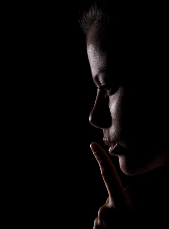 Young Woman Gesturing For Being Quiet, Shows Silence Sign In Dark Background photo