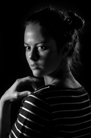 scared girl on black background, black and white image photo
