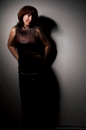 mature woman in leather brown dress with boa photo