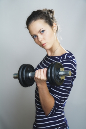 serious girl with dumbbell on gray background photo