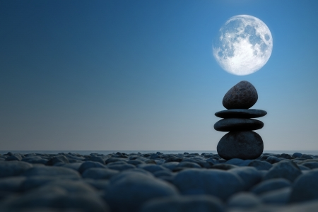 stacked stones in moonlight on pebble sea beach  Elements of this image furnished by NASA Stockfoto