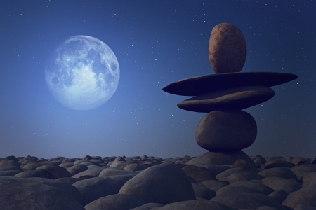 stacked stones in moonlight on pebble sea beach   photo