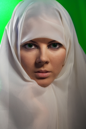 woman with green eyes in white hijab on green background looks in camera photo