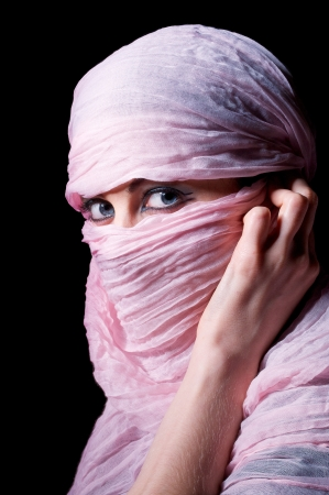 woman with blue eyes in pink hijab looks in camera photo