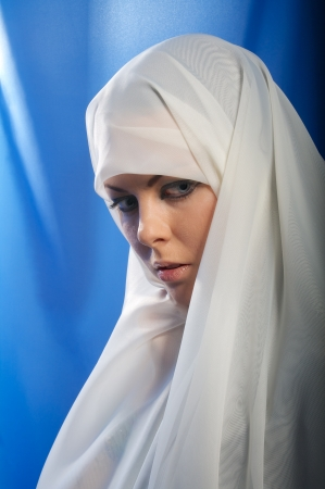 sad girl in white hijab looks down on blue background Stock Photo - 17749796