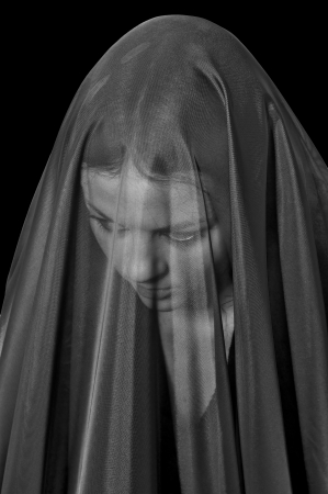 mourn: sad girl in mourning black veil isolated on black background, monochrome image