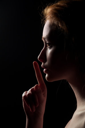 Young Woman With Red Hairs Gesturing For Being Quiet, Shows Silence Sign In Dark Background photo