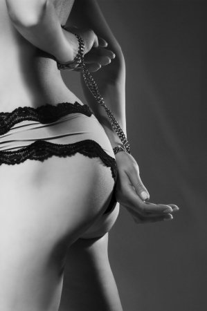 Female buttocks in lingerie with handcuffs from steel chain black white image Stock Photo