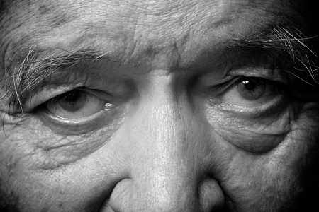 one mature man only: old man face part closeup eyes looks at camera monochrome image