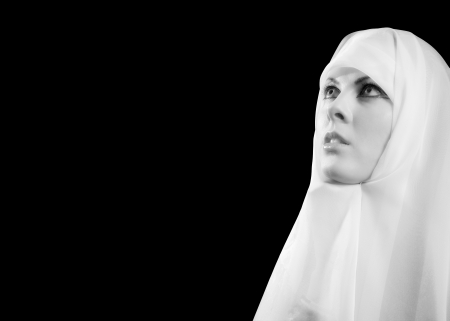 Nun in white praying looks up from dark monochrome image horizontal photo