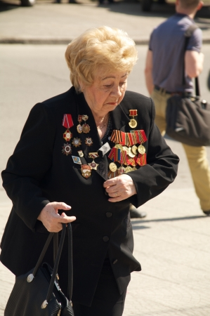 elder tree: Kaliningrad, Russia - May 05, 2013 - woman veteran of the World War with medals walk at street on during the victory celebration