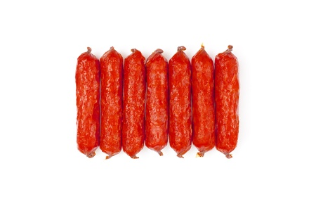 small smoked sausages stacked at a white background photo