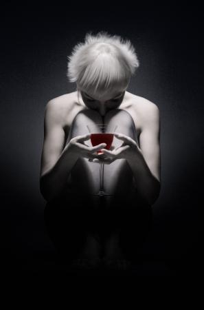 sad girl sitting in dark with red wine