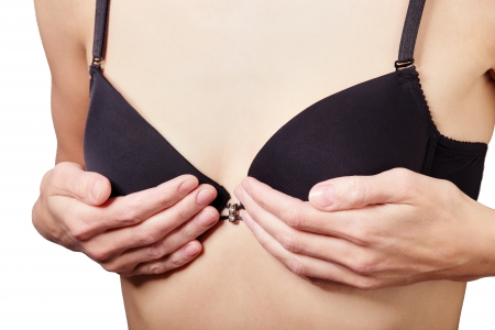 boobs: woman shows her small breasts in black bra isolated on white background Stock Photo