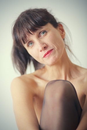 bared: smiling pensive mature woman with bared shoulders on white background Stock Photo