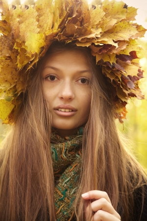 girl in yellow leaves crown plays with her long hairs photo