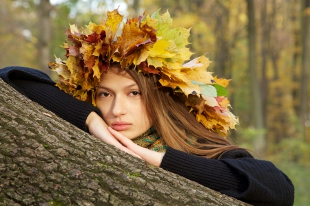 serious girl in yellow leaves crown looks at camera photo
