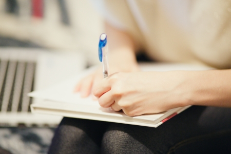 young woman's left hand with pen writing close-up