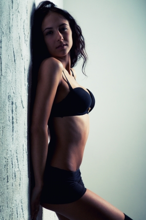 pretty girl in black bra posing near wall photo