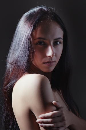 beautiful girl with long hairs sensual looking over shoulder in dark photo