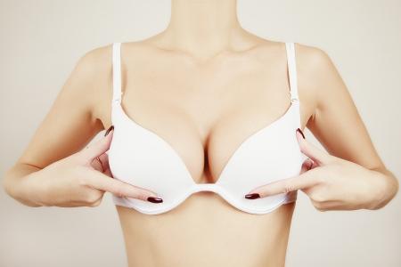 senos: chica mostrando mama en sujetador blanco Foto de archivo