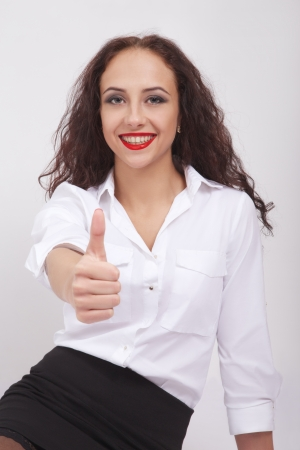 Close-up of a young woman showing thumb up photo