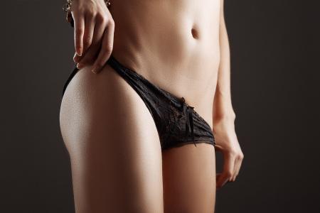 slim tan girl waist with black panties Stock Photo
