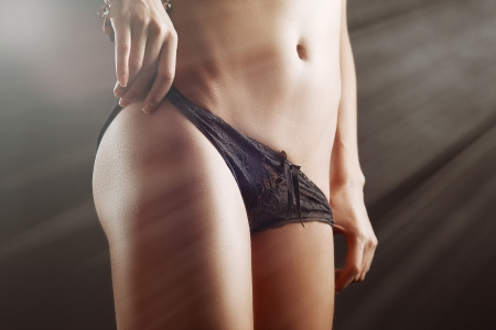 slim tan girl waist with black panties in light rays photo