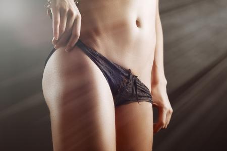 slim tan girl waist with black panties in light rays photo