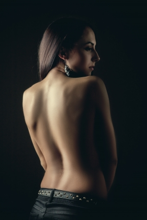 brunette woman bared back standing in dark photo