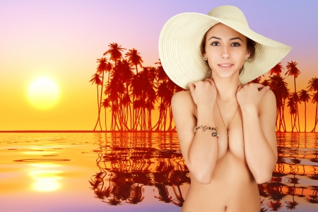 happy girl in straw hat near tropical sunset photo