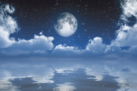 full moon between clouds over sea photo