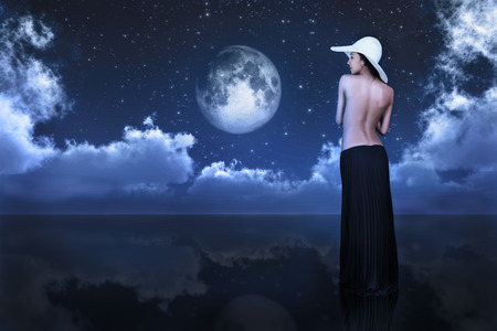 bare woman looking at full moon between clouds over water
