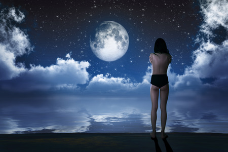 naked girl on sea beach looking at moon photo