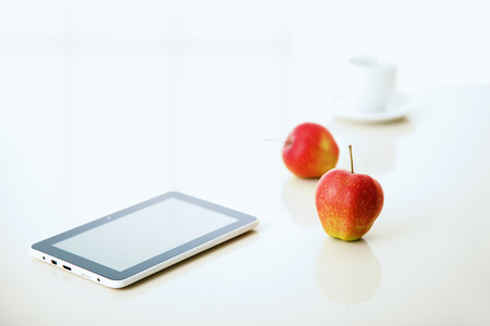 tablet pc with apple and coffee cup with reflections on table