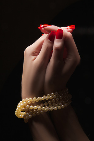 praying woman hands with necklace on black background photo