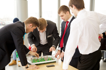 KALININGRAD, RUSSIA – MARCH 02, 2014: Businessmen plays in football table game on coffeebreak Editorial