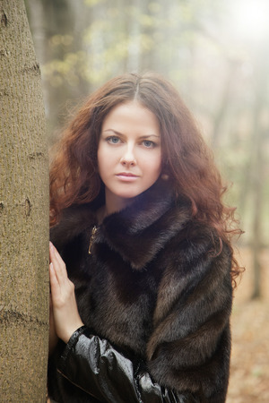 sad pensive girl in fur coat near tree  photo